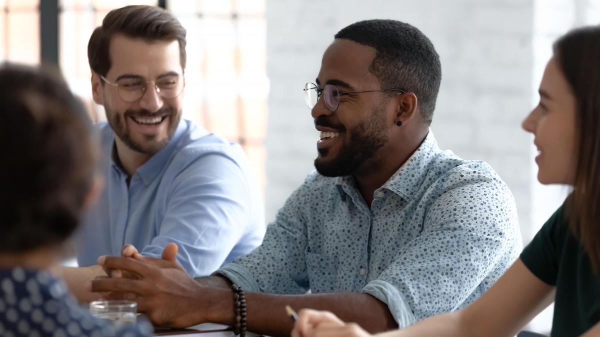 Karriere: Gruppe von Kollegen, die lächelnd in einem Meeting sitzen
