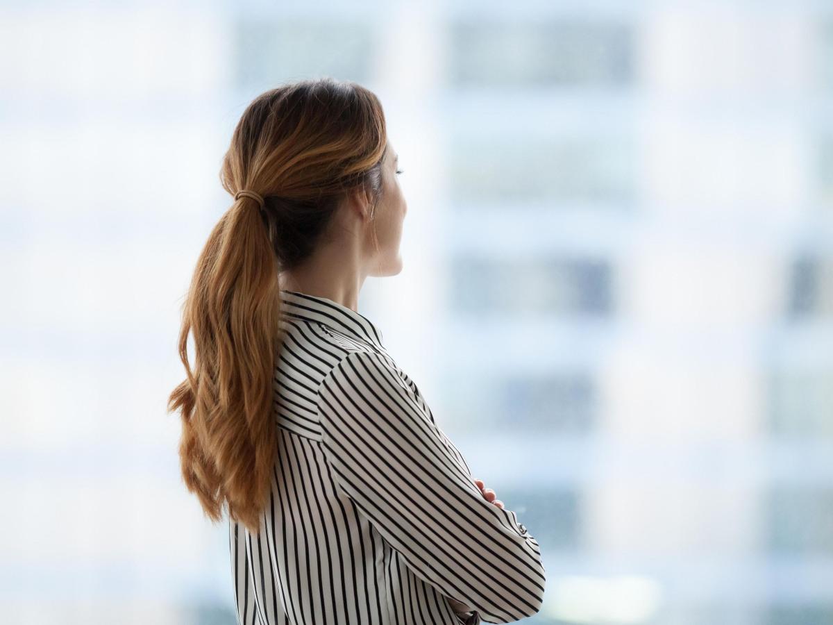 Unternehmen: Geschäftsfrau, die nachdenklich aus dem Fenster schaut