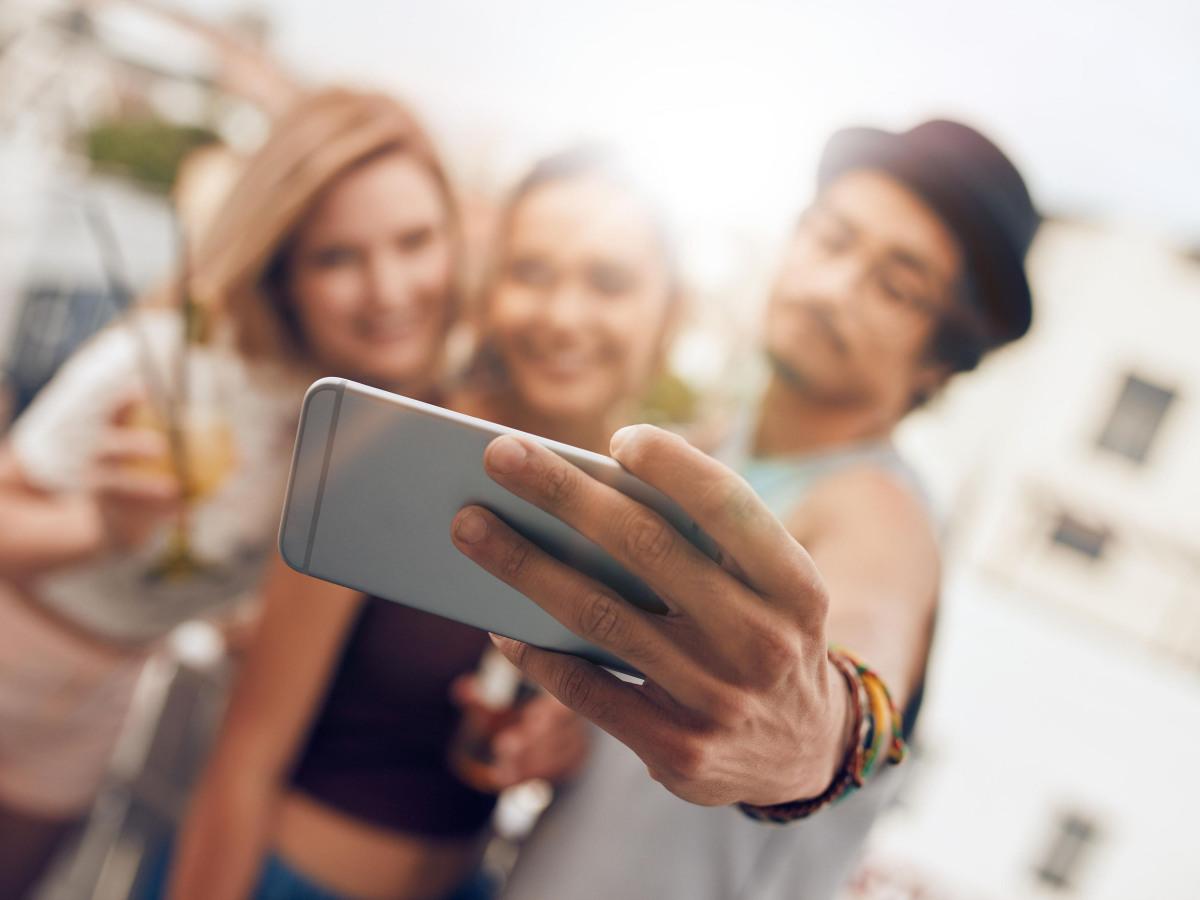 Presse: Gruppe junger Menschen, die mit ihrem Smartphone ein Bild von sich machen