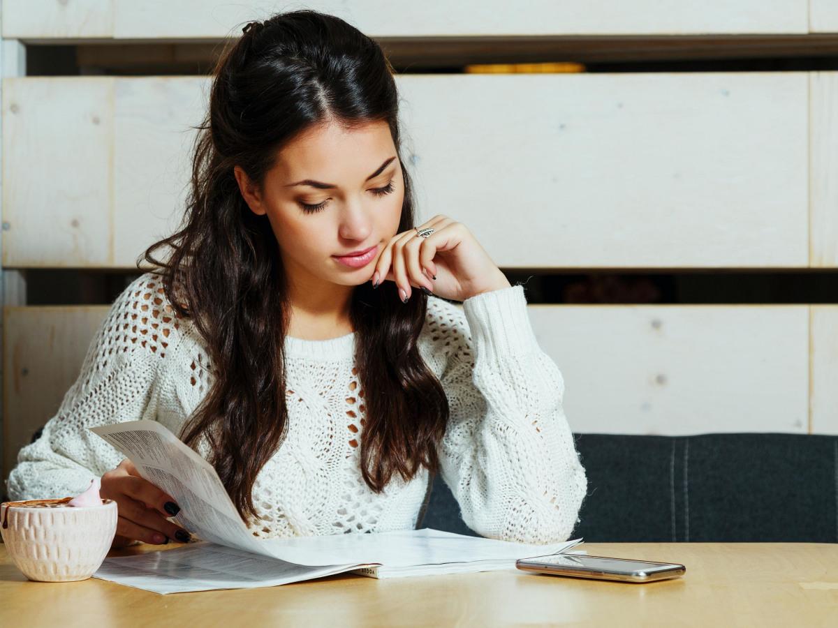 Newsletter: Eine junge Frau liest in einer Zeitung.