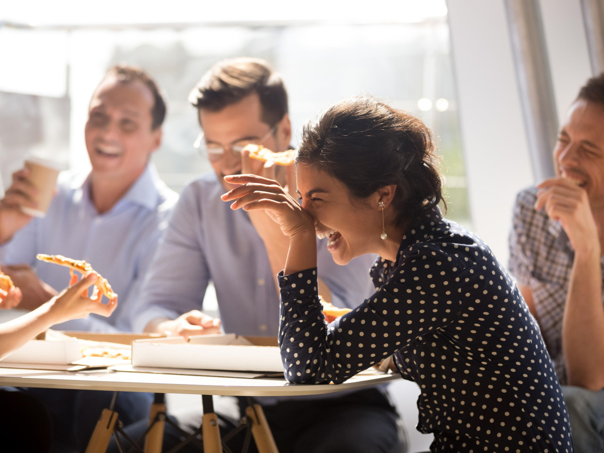 Gruppe von Arbeitskollegen, die zusammen sitzen und lachen