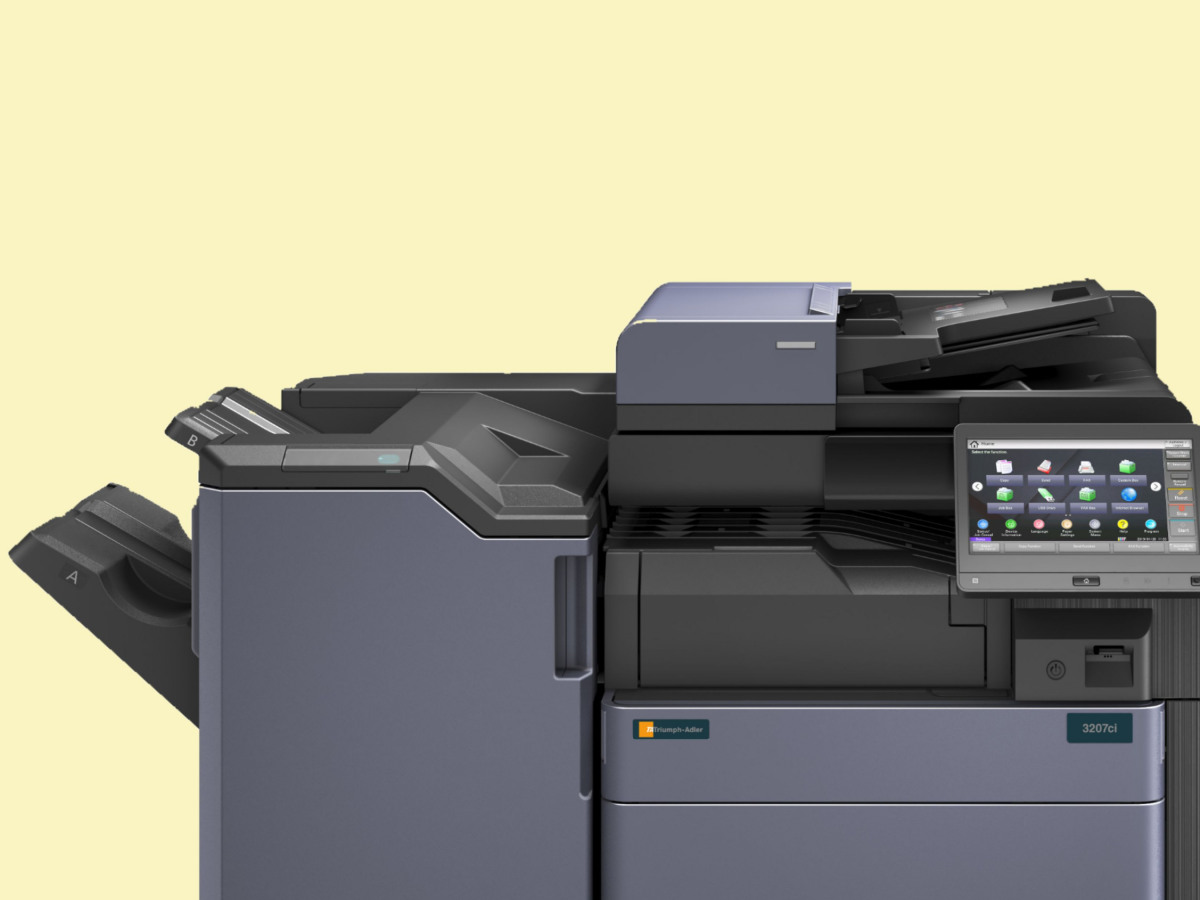 Anschnitt eines Triumph-Adler Multifunktionsprinters vor gelbem Hintergrund