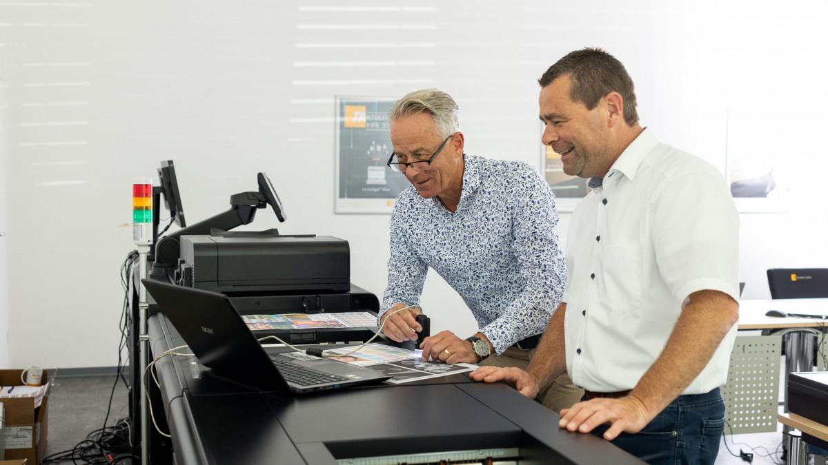 Zwei Männer stehen an der Produktionsdruckmaschine