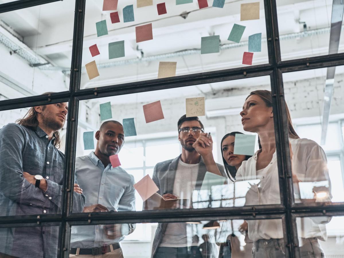 Workflows: Gruppe von jungen Menschen steht vor einer Glaswand mit Post-ITs