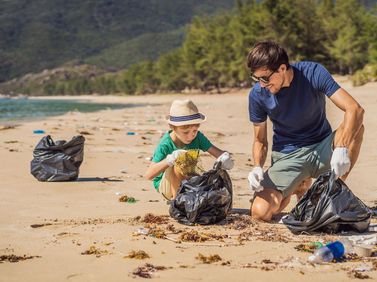 Tonerrücknahme: Vater und Sohn sammeln Müll an einem Strand