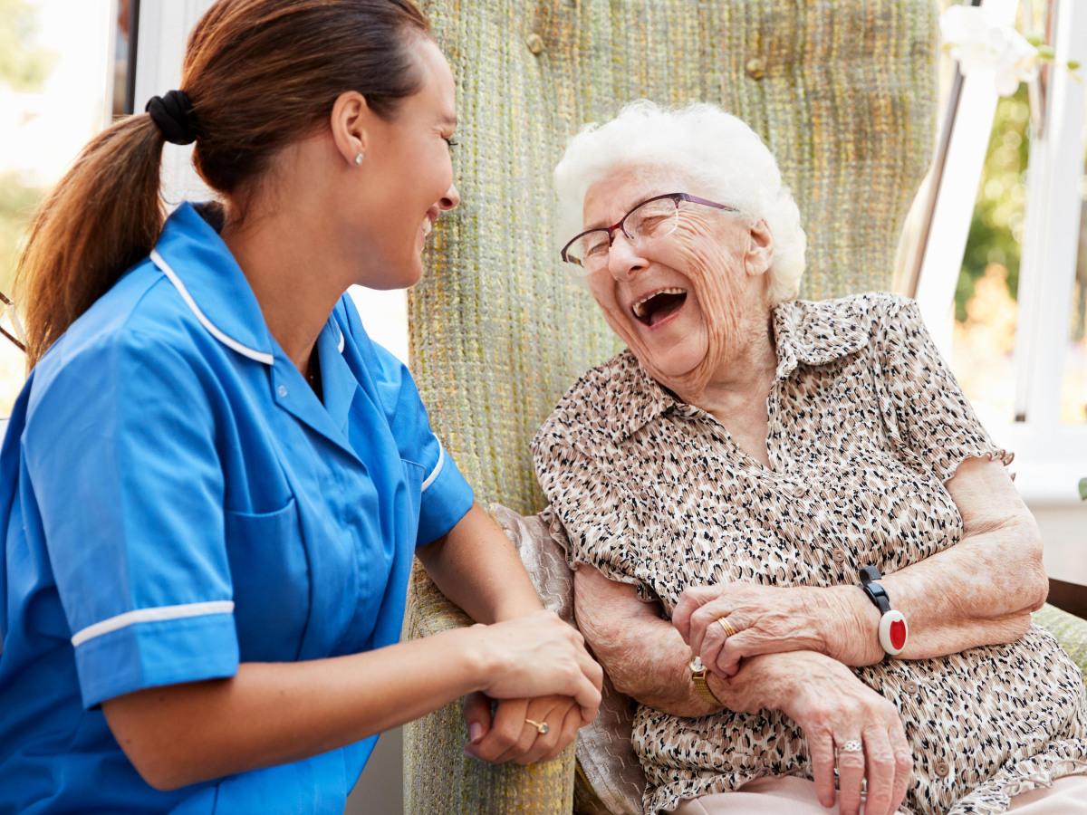 AÄltere Dame und eine junge Pflegerin, die zusammen lachen