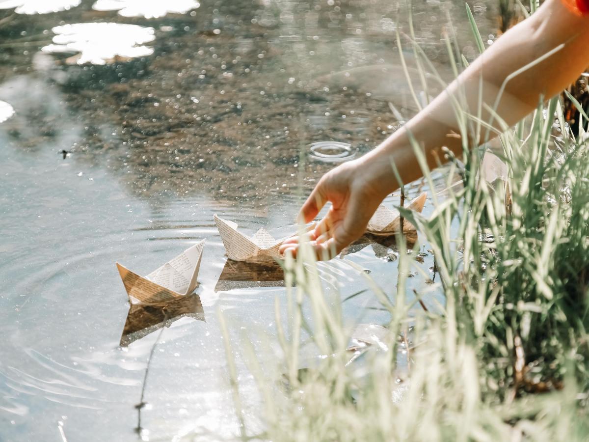 Nachhaltigkeit: Origamiboote, die in einen Fluss gesetzt werden