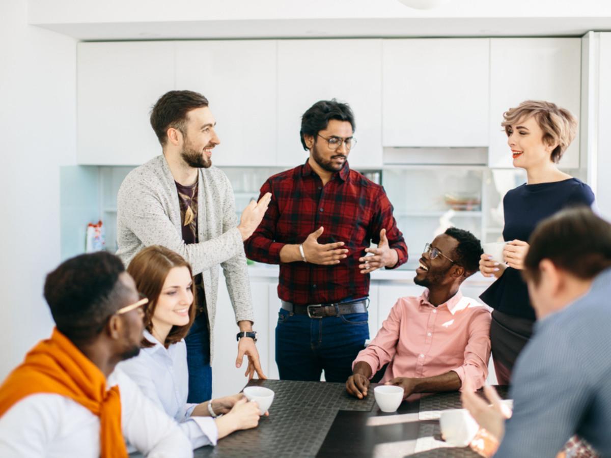 Arbeitskollegen, die in der Kaffeeküche zusammensitzen und stehen und sich unterhalten