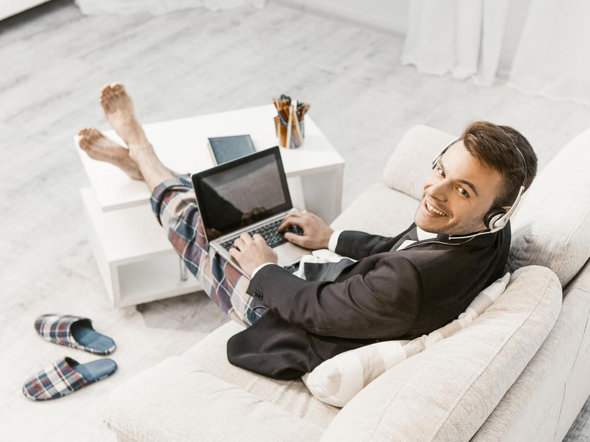 Aufnahme von oben auf einen Mann, der in Hemd und Jackett aber auch in Pyjamahose auf dem Sofa sitzt und in die Kamera schaut