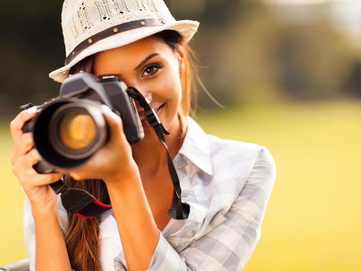 Mediathek: Nahaufnahme einer Frau, die durch ihre Kamera guckt und lächelt