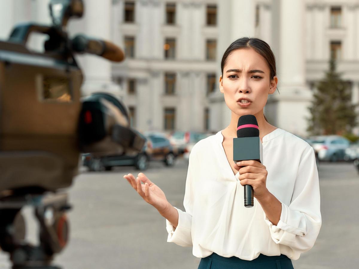 Presse: Schulterblick über einen Kameramann/-frau auf eine junge Reporterin