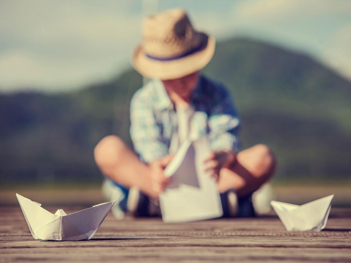 Umwelt: Kleiner Junge, der auf einem Steg sitzt und Papierboote faltet