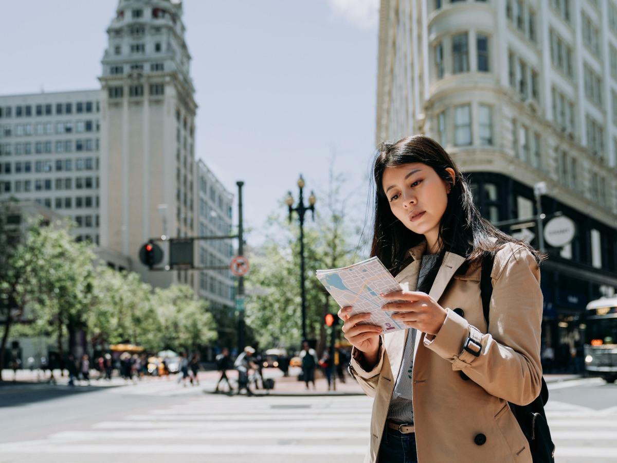 Standorte: Junge Asiatin, die auf eine Stadtkarte schaut