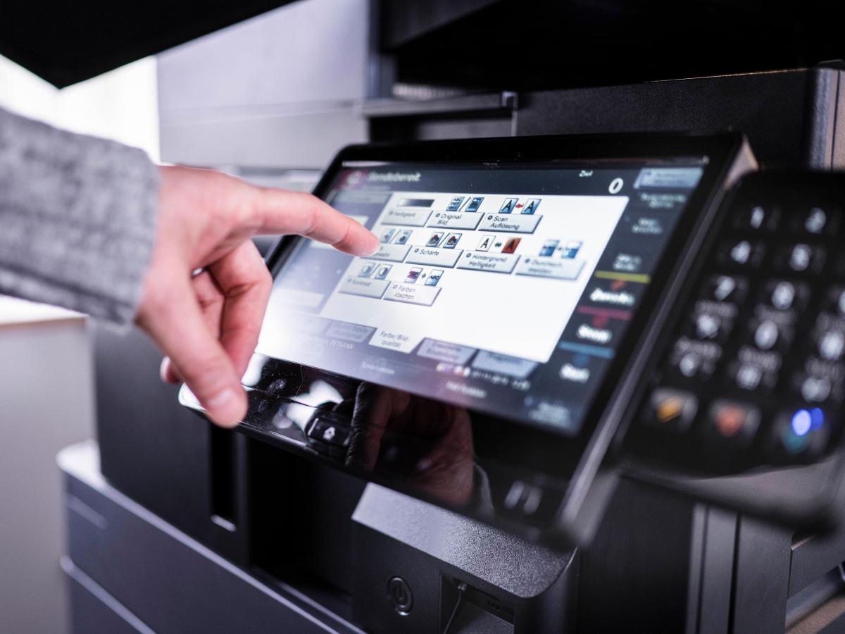 Nahaufnahme: Hand am Bildschirm eines unserer Multifunktionsprinter