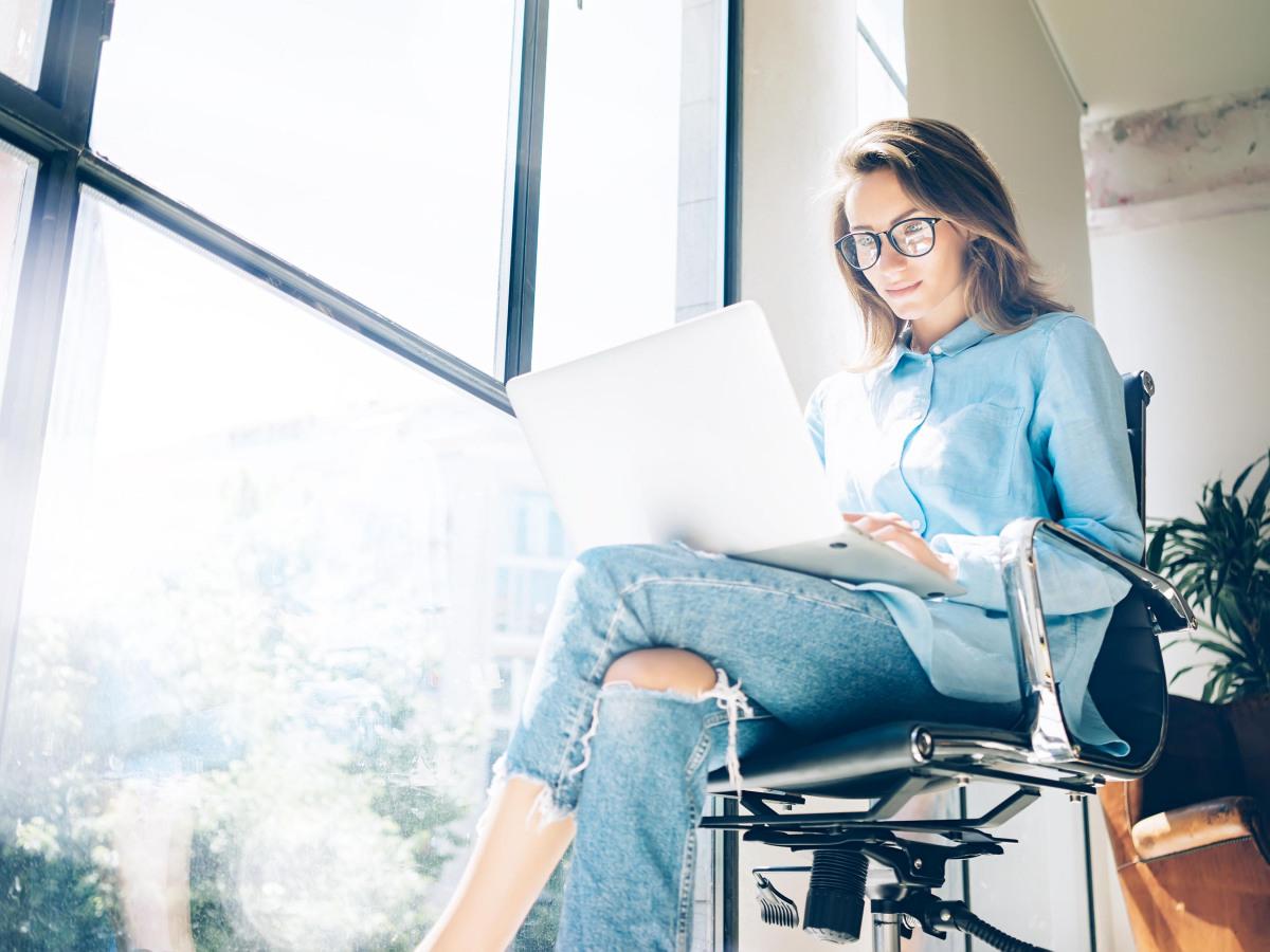 Digitalisierung: Eine Frau sitzt mit ihrem Laptop vor einer großen Fensterwand
