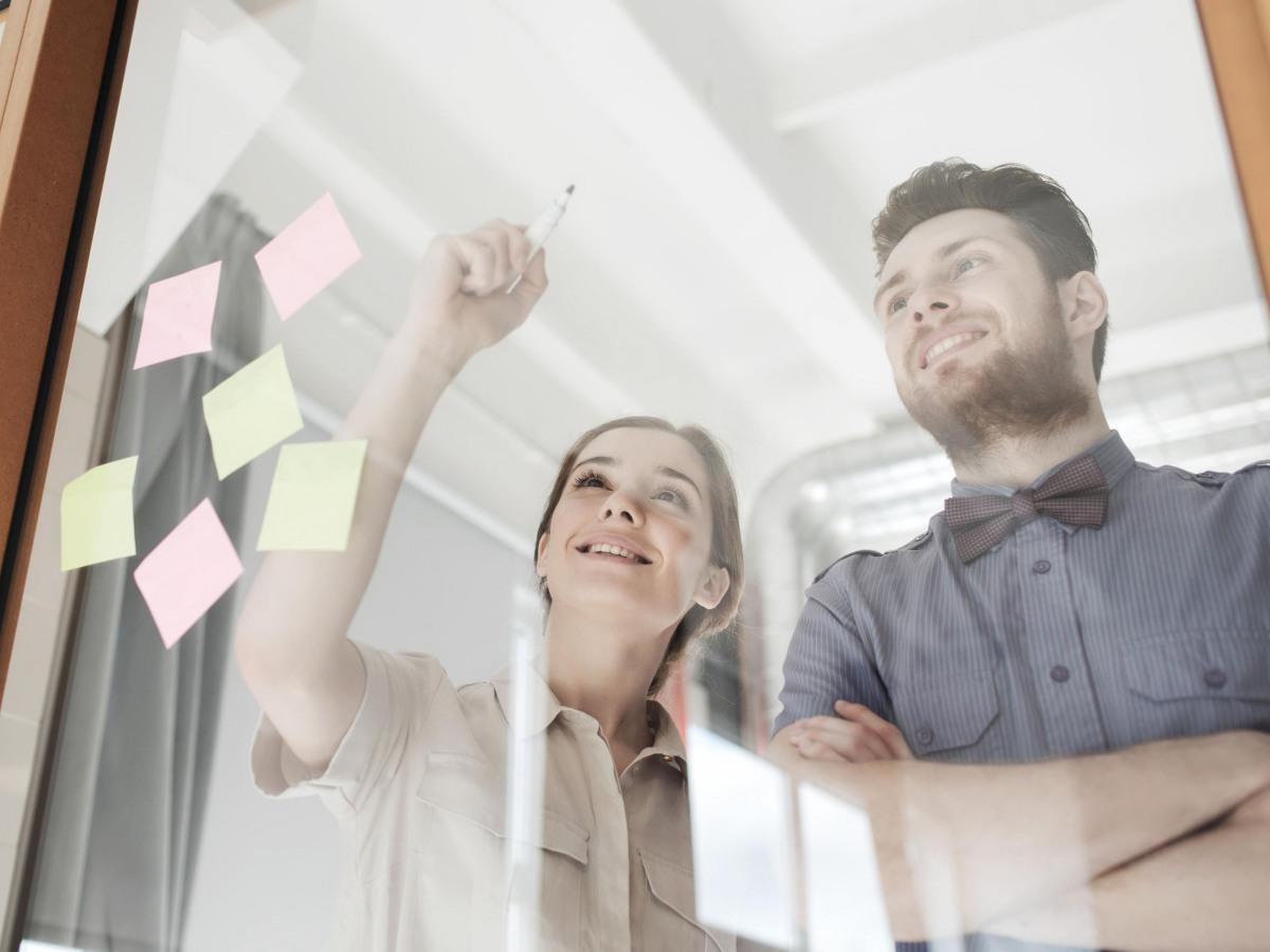 Workflows: Kollegen schreiben auf eine Glaswand