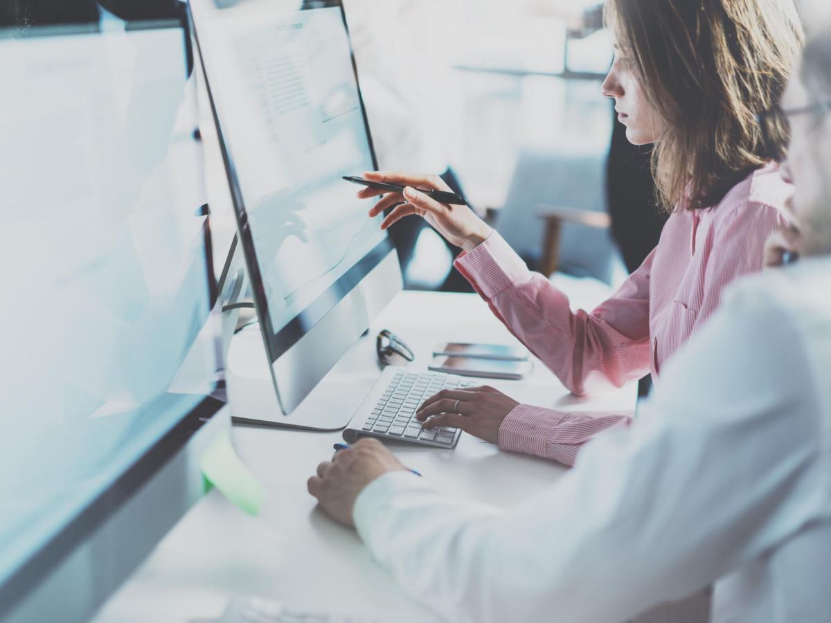 Datensicherheit: Kollegen sitzen vor dem Bildschirm und besprechen sich