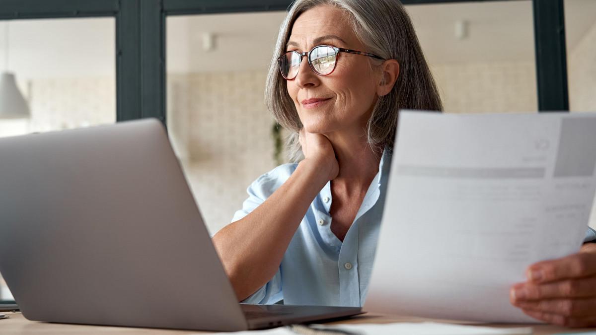 Digitalisierung: Ältere Dame sitzt lächelnd mit einem Papier in der Hand vor ihrem Laptop